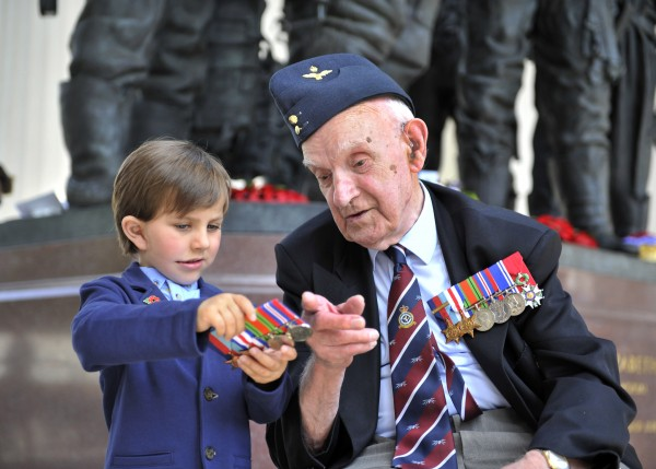 Left, Samuel Williamson, four, shows Bomber Command veteran Harry Rossiter his great great uncle Sgt Donald Eric Simmons' medals. Sgt Simmons was killed in action during the Second World War, on 25 July 1944