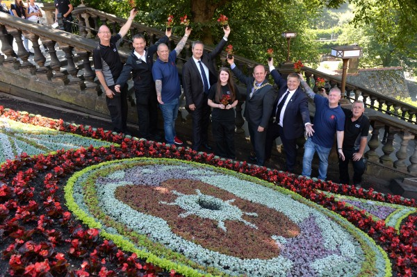 Photo caption:- All at the opening. Attending was the Lord Provost of Edinburgh and the Chief Executive Mark Bibby of Poppy Scotland. The finishing touches have been put to EdinburghÕs historic floral clock, which this summer has been designed to mark 100 years since the signing of the Armistice, leading to the end of the First World War. The West Princes Street Gardens landmark, maintained by the City of Edinburgh Council, has been created in partnership with Armed Forces charity Poppyscotland as part of their year-long fundraising campaign, The 1918 Poppy Pledge. On Tuesday (3 July), EdinburghÕs Lord Provost, Councillor Frank Ross, was joined by PoppyscotlandÕs Chief Executive Mark Bibbey, workers and ex-servicemen from PoppyscotlandÕs Lady Haig Poppy Factory, where all of the countryÕs five million poppies are made each year, and parks staff responsible for creating the clock. Together they officially unveiled the design, which features a poppy flanked by two First World War soldiers. PoppyscotlandÕs 1918 Poppy Pledge aims to commemorate those who fell in the First World War, with funds raised helping to provide support to those in the Armed Forces community. The Lord Provost, Councillor Frank Ross, said: ÒIt is an honour to be able to support the life-changing work carried out by Poppyscotland with this floral clock design, which this year will provide a particularly poignant reminder of the signing of the Armistice, 100 years on from the end of World War One. ÒAs always, I am delighted to officially unveil this striking and much-loved creation, which is a source of enjoyment and fascination for so many people every day, and IÕd like to congratulate our dedicated parks staff, whose hard work has paid off once again.Ó Gordon Michie, Head of Fundraising at Poppyscotland, said: ÒI am delighted that The City of Edinburgh Council has chosen to commemorate the signing of the Armistice this year by dedicating the world-famous Floral Clock to Poppyscotland and our work supporting beneficiaries across Scotland. ÒThis support, which is part of our wider #1918PoppyPledge campaign, will give a unique, powerful and emotive view of Remembrance in the vibrancy and colour of the 35,000 flowers that have been planted. It will be a place to not only visit and take photographs, but also a place to reflect on the sacrifices that so many gave on our behalf. Furthermore, it is fitting that the floral clock is situated close to so many other monuments in West Princes Street Gardens to those that have served.Ó The floral clock was first created in 1903 by the Edinburgh Parks Superintendent, John McHattie. The clock initially operated with only an hour hand with a minute hand added in 1904, followed by an accompanying cuckoo clock in 1952. Until 1972 the clock was operated mechanically, and had to be wound daily. Since 1946 it has been designed in honour of various organisations and individuals, including the Girl Guides Association, Robert Louis Stevenson and the Queen, for her Golden Jubilee. It has taken two gardeners more than a month to plant the 35,000 flowers and plants used to create the clock, which will be in bloom until October. Poppyscotland provides life-changing support to the Armed Forces community, with money raised from the Scottish Poppy Appeal and year-round fundraising enabling the charity to provide tailored funding and assistance, as well as advice, employment, housing, healthcare and respite. Find out more about EdinburghÕs parks and green spaces online. Floral clock fact file The clock was created in 1903 May Ð when planting begins 35,000 plants are used in the design (compared to 13,000 in 1930s; 25,000 50s-60s) 1952 Ð when the cuckoo was added In 1946 the clock began celebrating a different event or anniversary Clock circumference: 36 ft Clock width: 11 ft 10 ins 80lbs Ð weight of large hand 50lbs Ð weight of small hand 1973 Ð when the clock began being operated electrically EdinburghÕs is believed to be oldest floral clock in the world